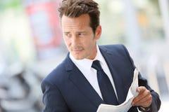 英俊的商人读书报纸 免版税图库摄影
