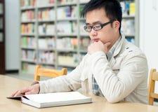 英俊的图书馆人读取开会 免版税图库摄影