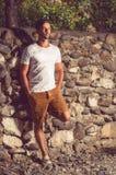 英俊的在一个石墙附近的人常设外部 库存照片