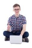 英俊的在丝毫隔绝的十几岁的男孩使用膝上型计算机的和赞许 库存照片