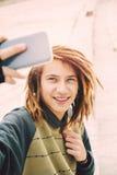 英俊的在城市温暖的过滤器的rasta青少年的人selfie申请了 库存图片