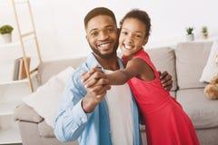 英俊的在家跳舞父亲和逗人喜爱的女儿 免版税库存图片