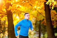 年轻英俊的在晴朗的秋天自然的运动员连续外部 免版税图库摄影