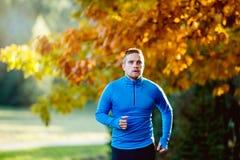 年轻英俊的在晴朗的秋天自然的运动员连续外部 免版税库存图片