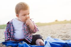 英俊的好奇孩子坐在海滩的沙子 免版税库存照片