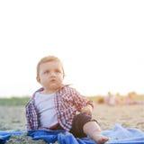 英俊的好奇孩子坐看天空的海滩 库存照片