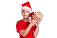 英俊的好奇男孩,在他的头的圣诞老人帽子,检查礼物盒 概念:圣诞节或新年快乐假日 免版税库存图片