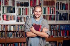 英俊的学员在图书馆里 免版税库存图片