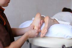 英俊的实践的男按摩师揉女性客户的脚,锂 免版税库存照片