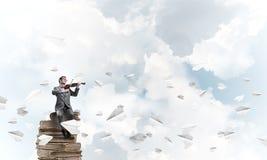 英俊的小提琴手戏剧他的曲调和纸飞机飞行  免版税库存图片