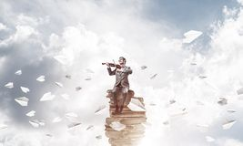 英俊的小提琴手戏剧他的曲调和纸飞机飞行  库存照片