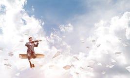 英俊的小提琴手戏剧他的曲调和纸飞机飞行  库存图片