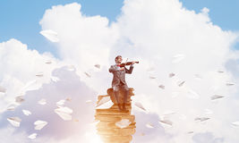 英俊的小提琴手戏剧他的曲调和纸飞机飞行  免版税库存照片