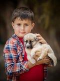 英俊的小男孩拿着一条狗 特写镜头纵向 库存图片
