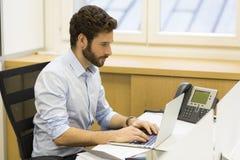 英俊的工作在计算机上的办公室的行家有胡子的人 库存照片