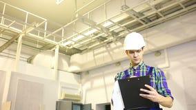 英俊的工程师研究他的项目 他拿着一张图纸并且周道地看得在旁边 股票视频