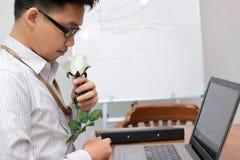 英俊的年轻亚裔商人一朵白色玫瑰为他的女朋友做准备在情人节 爱和浪漫史在工作场所conce 免版税库存图片