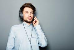 英俊的年轻人佩带的耳机和听到音乐 免版税图库摄影