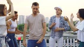 英俊的年轻人在朋友圈子跳舞获得在屋顶的乐趣在露天党 庆祝,活跃 股票视频