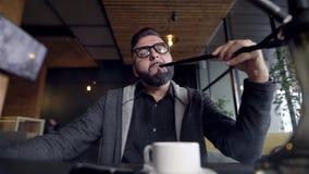 英俊的年轻人在白天的一家餐馆抽水烟筒,呼气抽烟在照相机,站立在桌上 股票录像