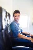 英俊的年轻人在船上在飞行期间的一架飞机 免版税库存图片