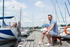 英俊的年轻人坐在码头的长凳在被停泊的小船之间 年轻商人在度假在码头的 图库摄影