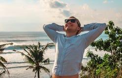 英俊的年轻人放松靠近清楚的蓝色海洋和山在日落 城市立陶宛palanga街道主题旅行 热带海滩的人与 免版税库存图片