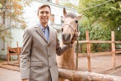 英俊的年轻人爱抚一匹浅褐色的马在农场 免版税库存照片