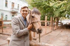 英俊的年轻人爱抚一匹浅褐色的马在农场 库存照片