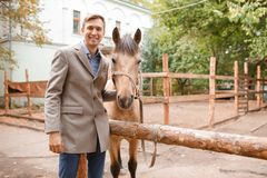英俊的年轻人爱抚一匹浅褐色的马在农场 免版税库存图片