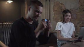 英俊的年轻人获得乐趣在情感地打电子游戏的晚上在他的研究膝上型计算机的女朋友附近在现代 影视素材