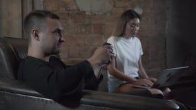 英俊的年轻人获得乐趣在情感地打电子游戏的晚上在他的研究膝上型计算机的女朋友附近在现代 股票视频