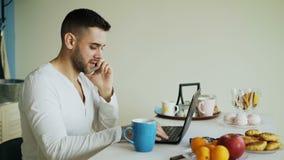 英俊的年轻人谈的电话和使用坐在厨房里在早餐以后的便携式计算机早晨 股票视频