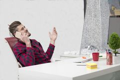 英俊的年轻人谈话在电话,当做文书工作在工作场所时 库存照片