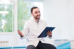 英俊的年轻医生画象在办公室 免版税库存图片
