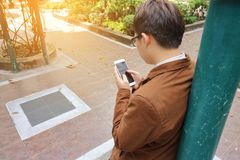 英俊的年轻商人在他的手上的看手机,当倾斜与阳光作用的一根杆室外时 免版税库存照片