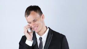 英俊的年轻商人谈话在智能手机 库存图片