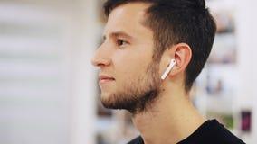 英俊的年轻在电话的商人听的音乐使用无线耳机 股票录像
