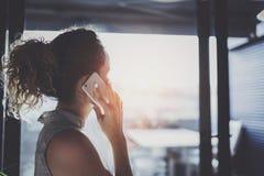 英俊的年轻女人谈话与朋友通过现代智能手机,当花费她的时间在现代都市咖啡馆时 图库摄影