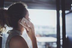 英俊的年轻女人谈话与朋友通过现代智能手机,当花费她的时间在现代都市咖啡馆时 免版税图库摄影