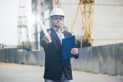 英俊的年轻建造者和建筑师研究一个新的项目 免版税库存图片