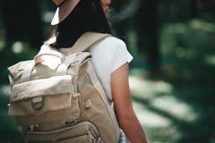英俊的年轻旅客女孩举行定位图在手和看起来上定向方式旅行的与背包 库存照片