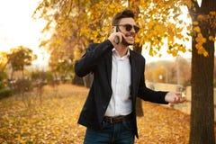 英俊的年轻时髦的男性商人愉快和微笑的谈话在电话 库存照片