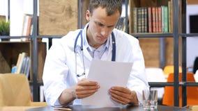 英俊的年轻正面医生学习在他的诊所的医疗报告 免版税库存图片