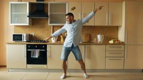 英俊的年轻滑稽的人跳舞在厨房在家早晨和获得乐趣在度假 免版税库存照片