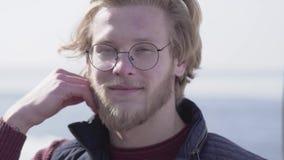 英俊的年轻白肤金发的人特写镜头玻璃的与看在照相机的蓝眼睛接触他的头发 可爱的人 股票视频