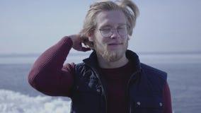 英俊的年轻白肤金发的人特写镜头画象看的玻璃的接触他的头发 斯堪的纳维亚人的可爱的人 股票视频