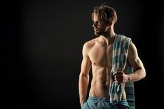英俊的年轻运动员身分一半赤裸与在脖子,拷贝空间的毛巾 免版税库存照片