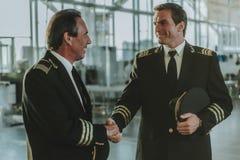 英俊的年轻飞行员欢迎与他的同事 免版税库存图片