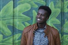 英俊的年轻黑人在被绘的墙壁前面微笑 免版税图库摄影